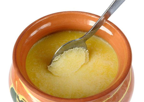 Melted butter in a clay pot on a white background