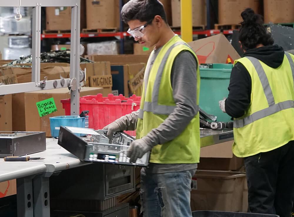 Westech worker dismantling a computer