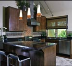 """LED track lighting and pendant lighting, bamboo wood flooring border around the cabinets and a """"green"""" river rock backsplash. Photo Est Est Incorporated"""